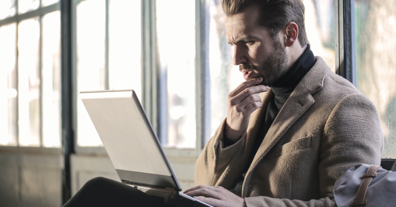 A guy in the business suit wondering about something in front of his laptop.