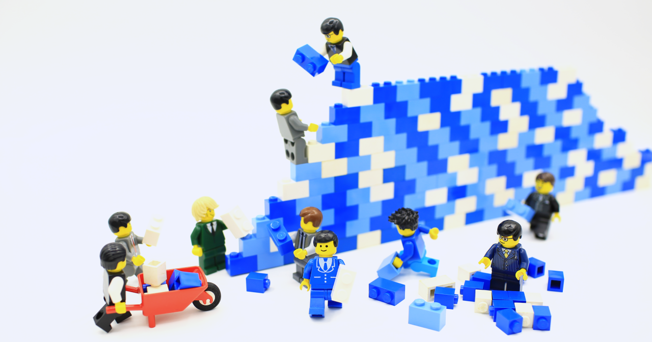 Lego minifigures building a construction from lego bricks