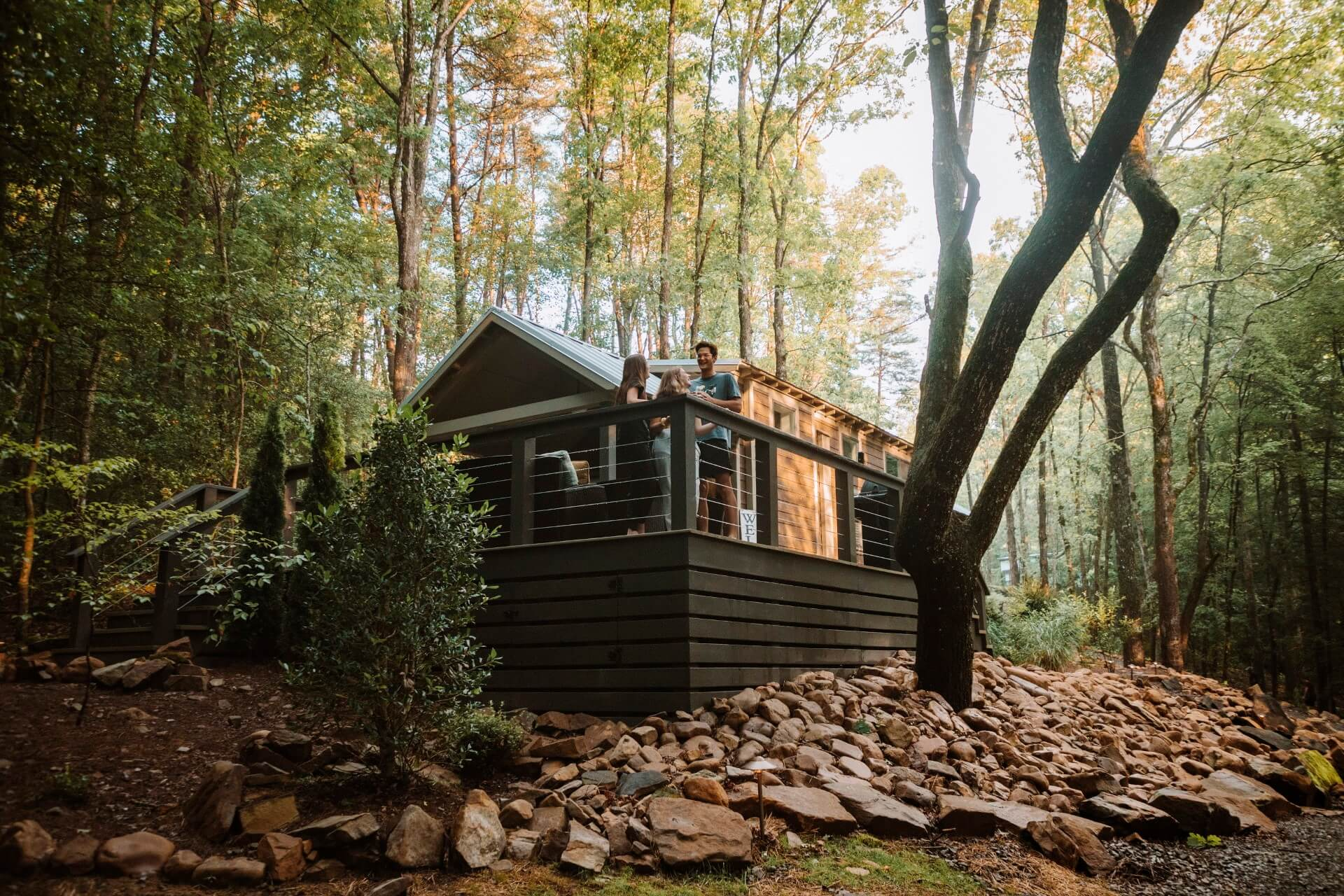 3 friends laughing on the deck of a tiny home