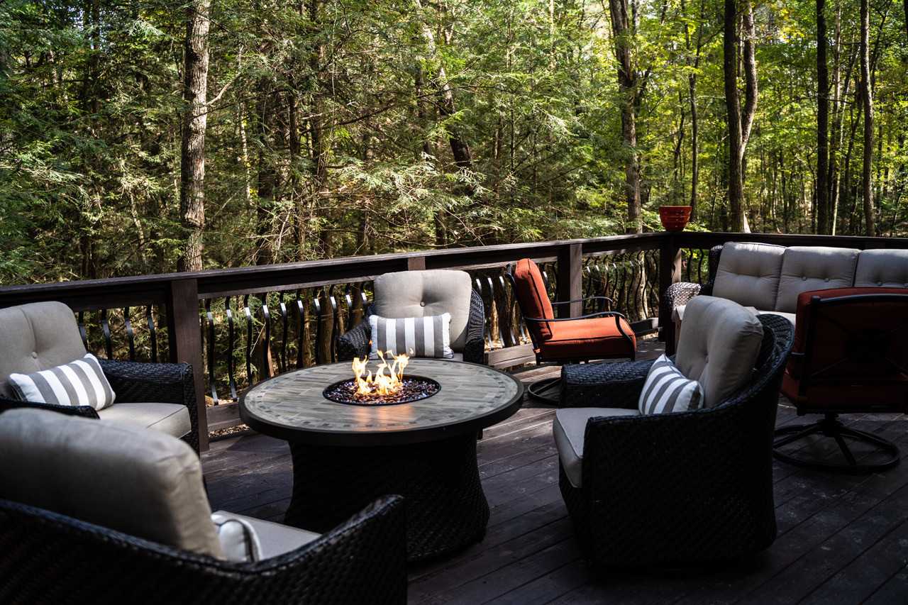 Several chairs surrounding a firepit on the deck of a tiny home in the woods
