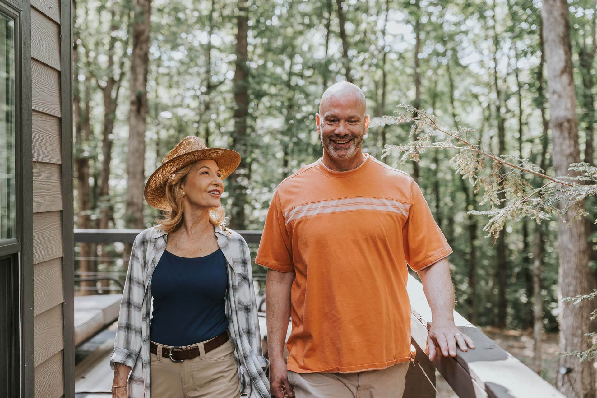 A couple smiling while walking on a tiny house deck