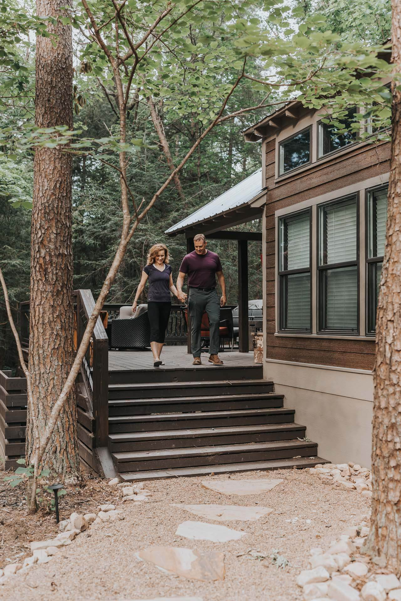 A couple walks down the steps of a tiny home in the woods