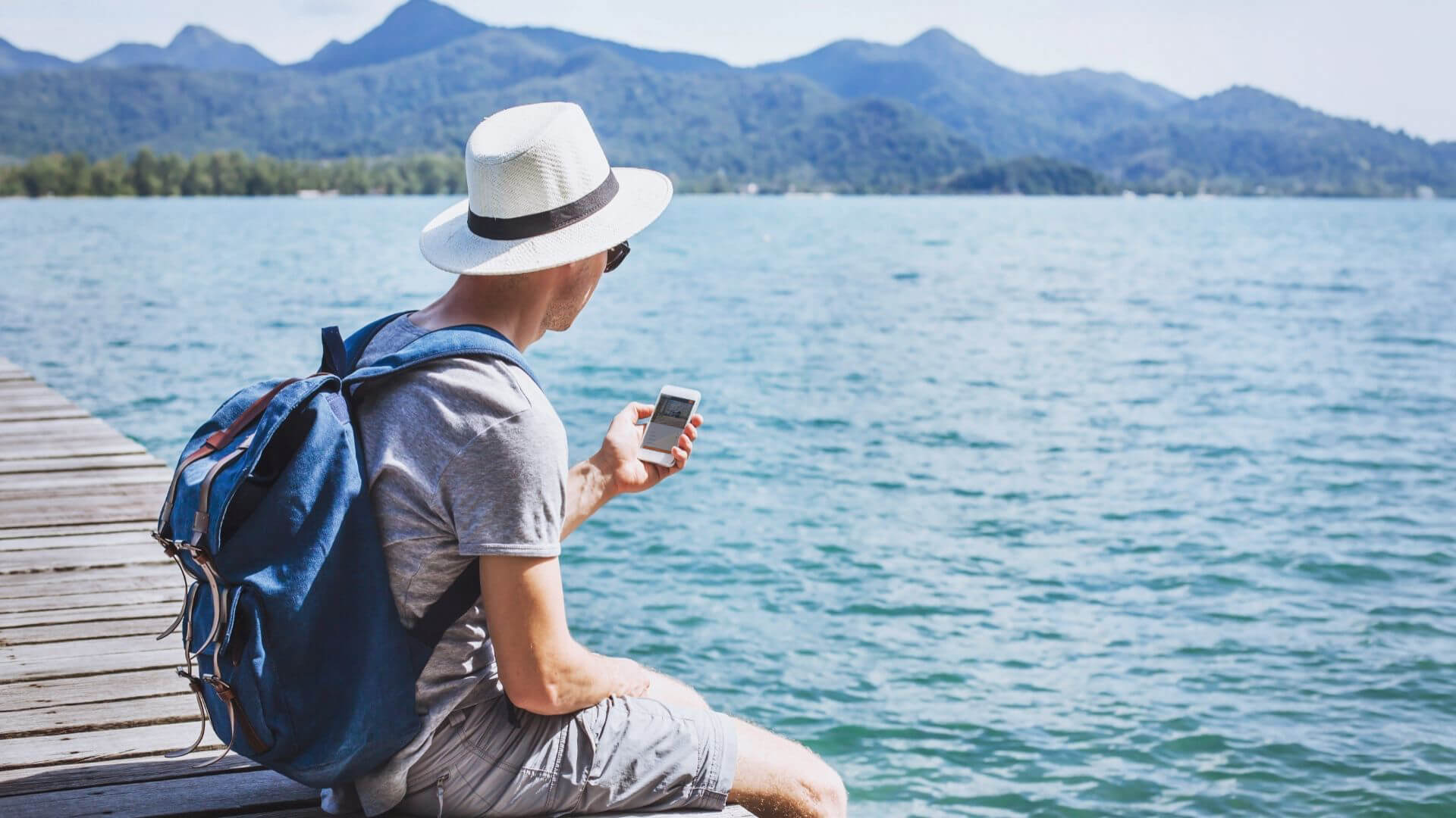 A man wearing a hat sitting on a dock with his legs over the water using his phone