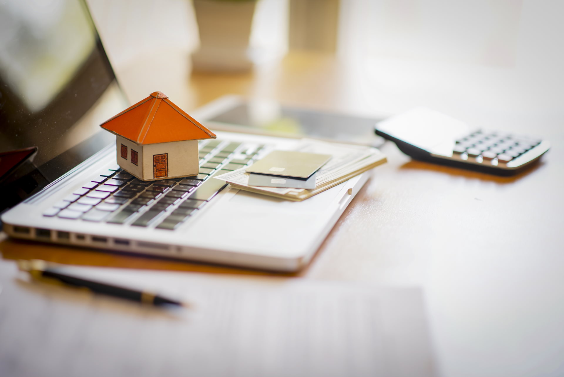 A laptop, a calculator, and financial documents along with a small house model.