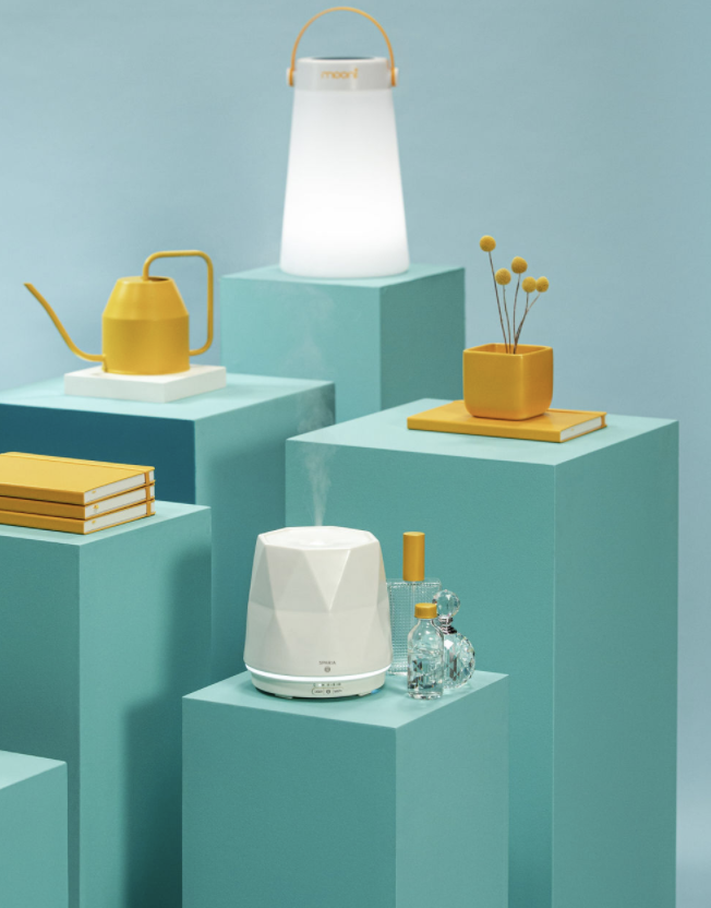 Photo of yellow humidifier, lamp, flowers, and tea kettle on turqouise blue pedestals
