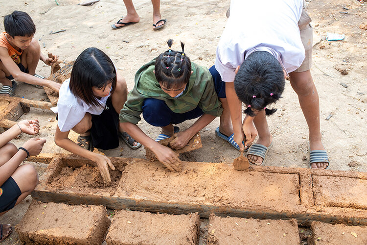 Kids and the community help mould mud bricks..jpg