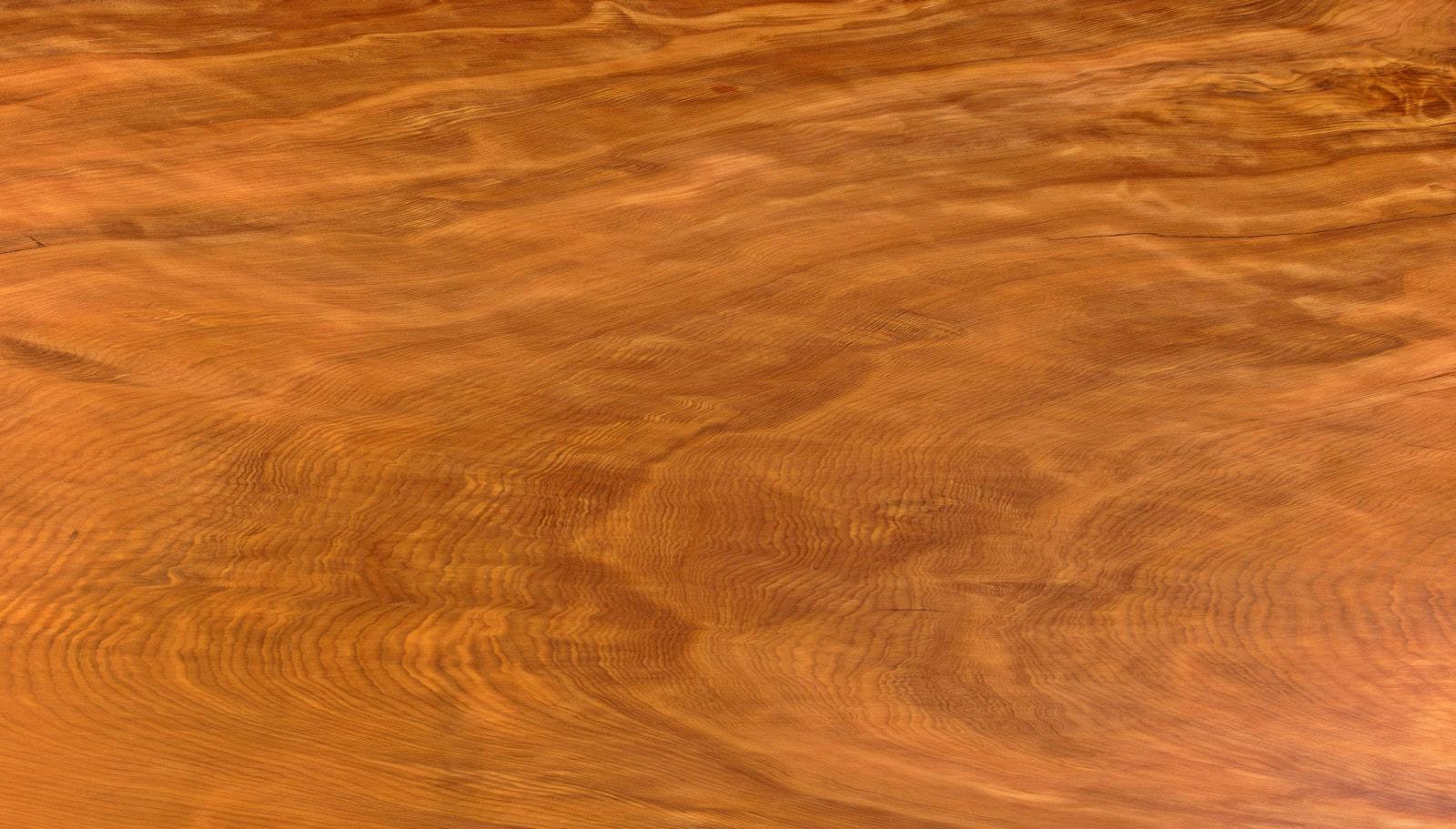 Maserung vom tausendjährigen Kauri Holz eines großen Massivholztisches mit organischen Naurkanten