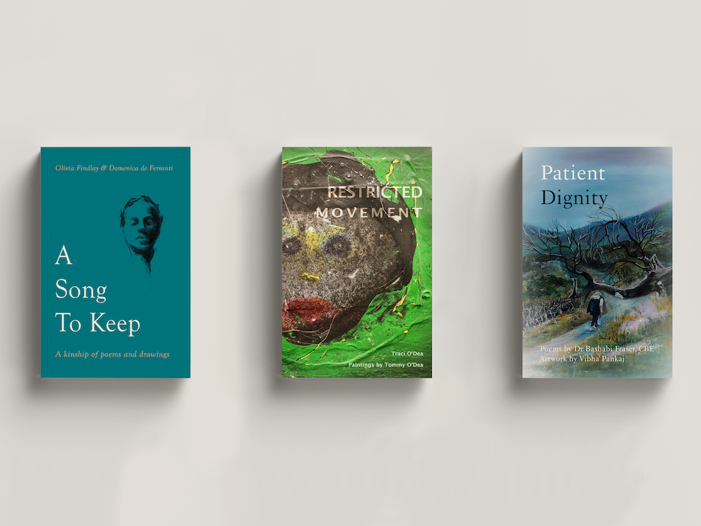 Three poetry books in a row on a plain background