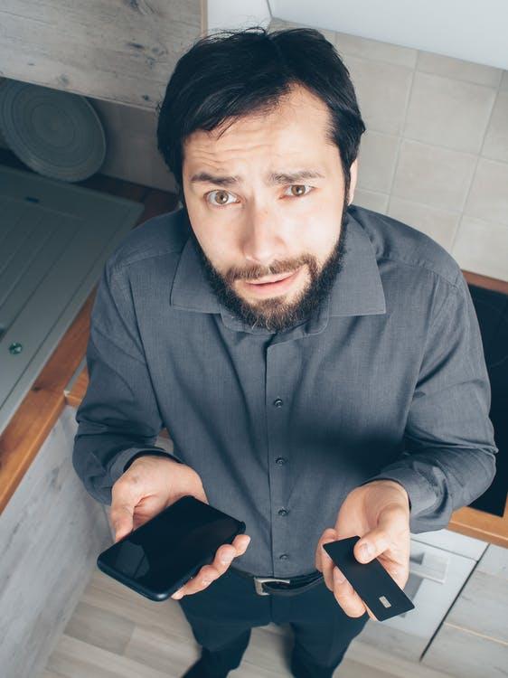 Mężczyzna W Koszuli Czarnej Sukni Trzymając Czarny Smartfon