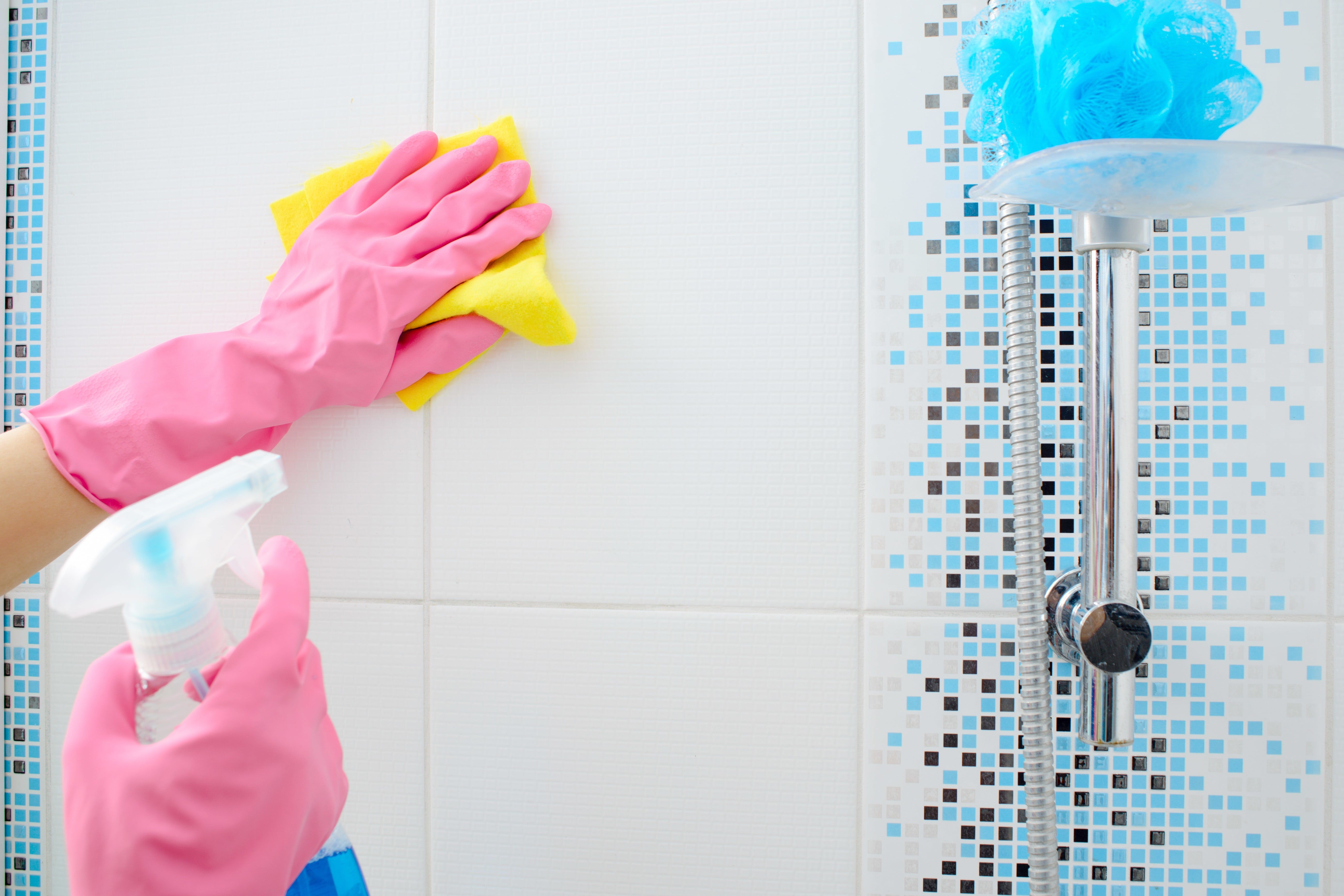 Bathroom wall cleaning in gloves