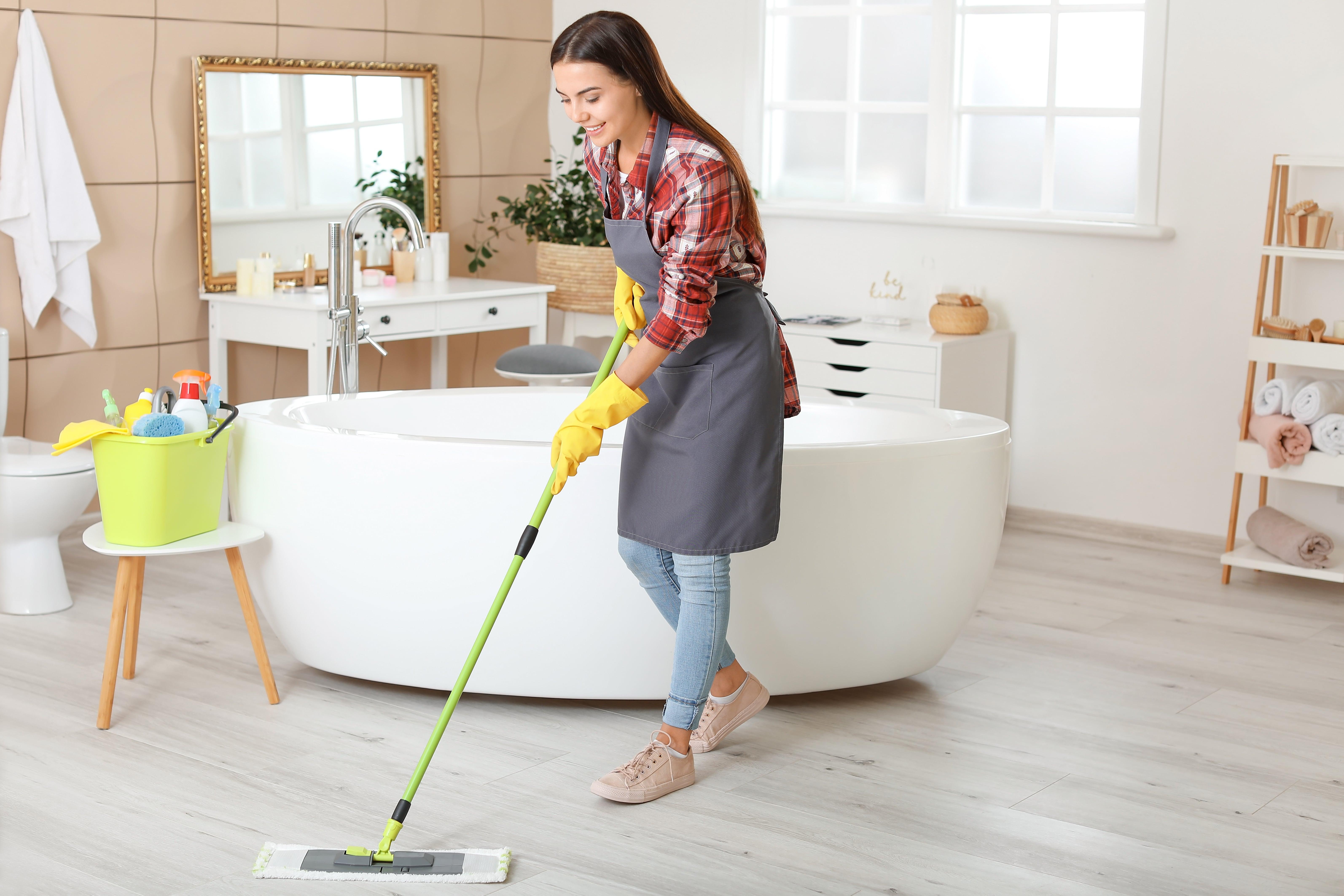 Woman is cleaning bathroom floor