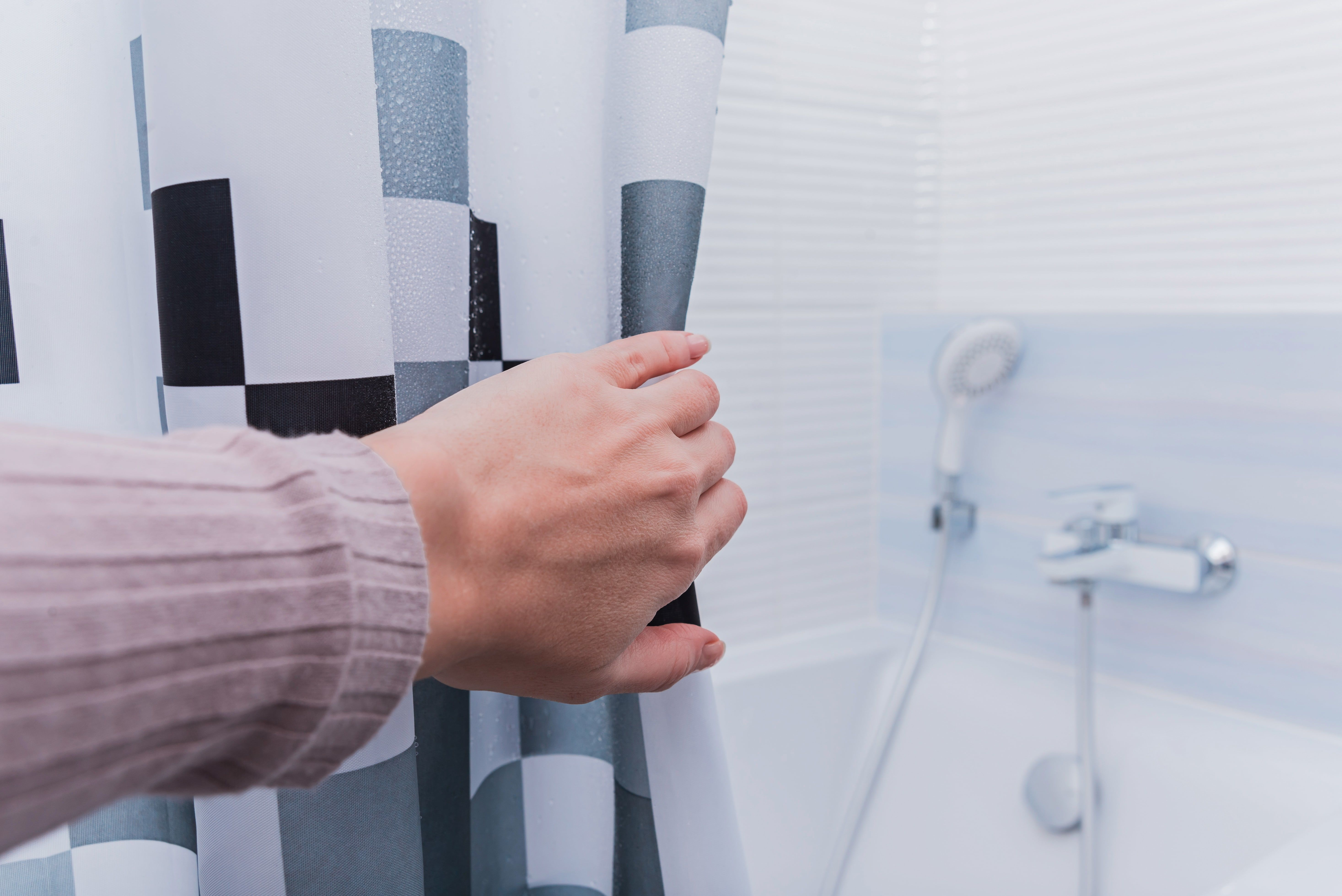 A woman is holding a shower curtain