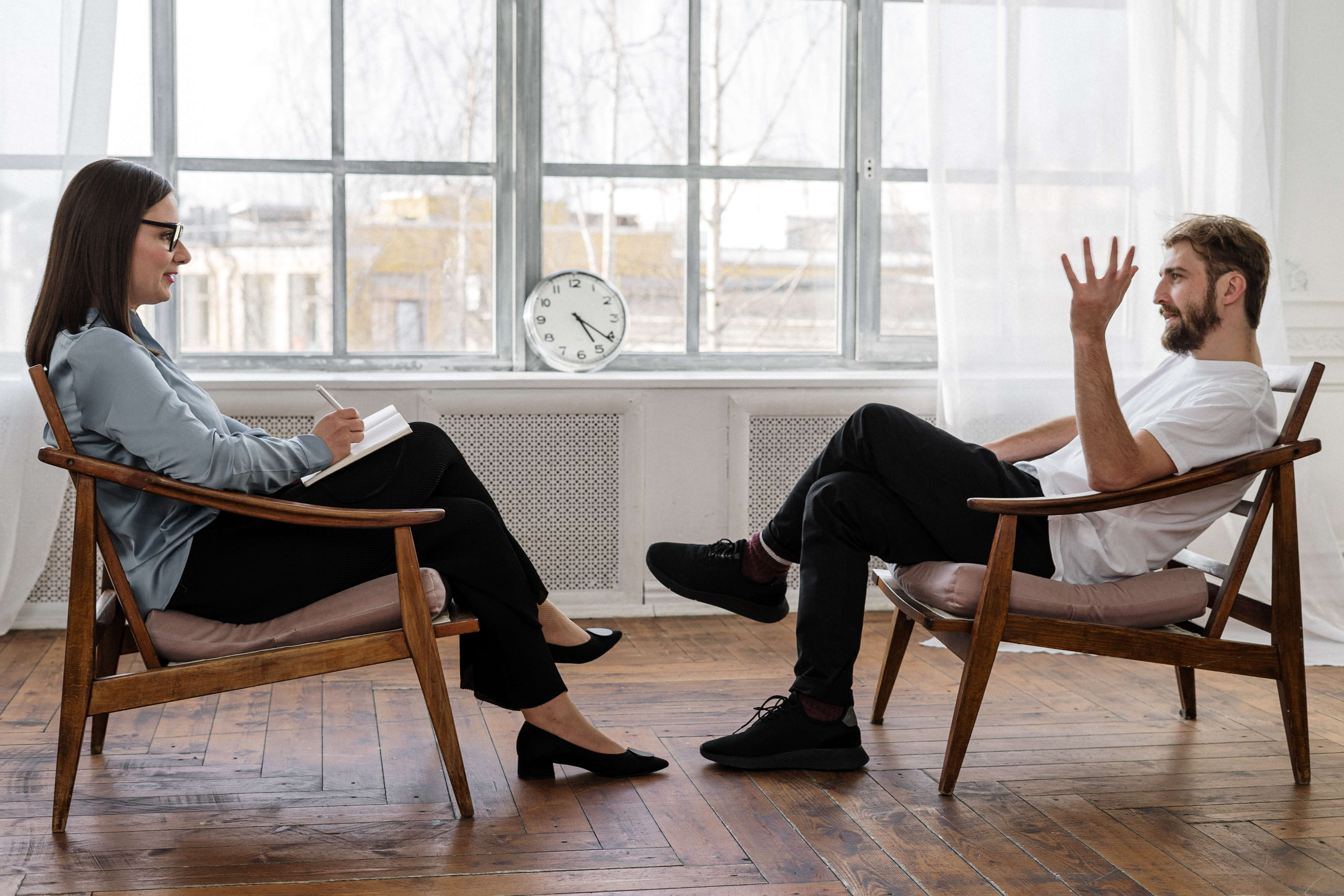 two people sitting in chairs  face to face