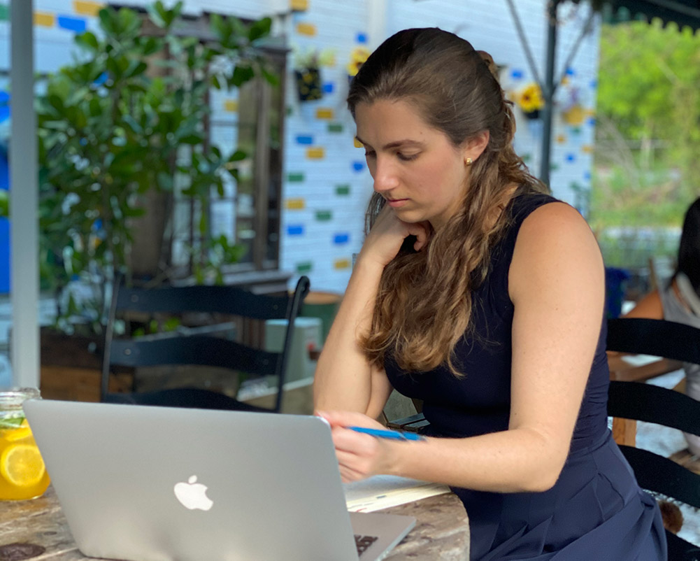 Nicole dressed in navy blue, sitting in front of a table outdoors, writing on her notebook, with a laptop.