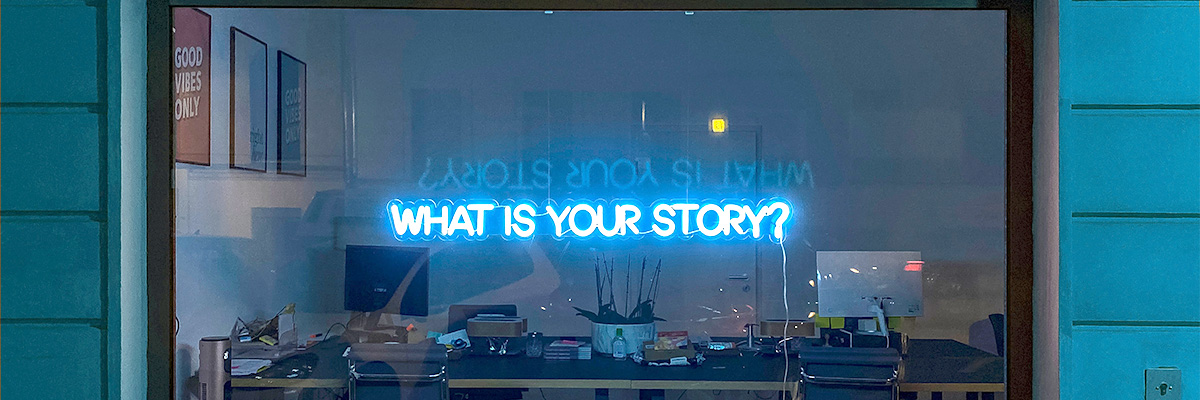 """A neon sign that says """"What is your story?"""" placed on an office window"""