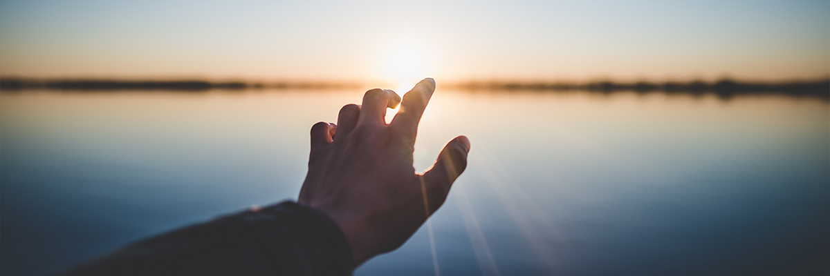A hand reaching into the distance, a lake with the sun setting in the background