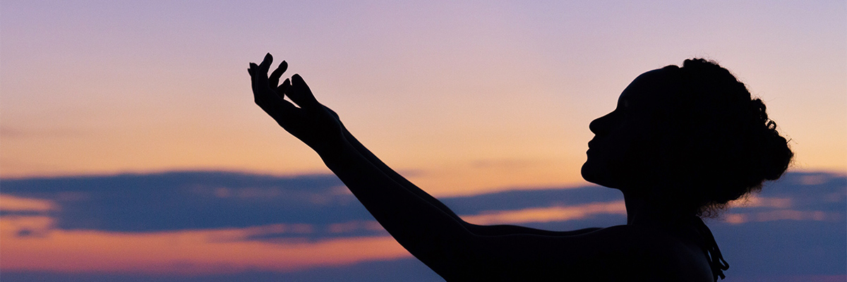 A silhouette of a woman with the sunset in the background