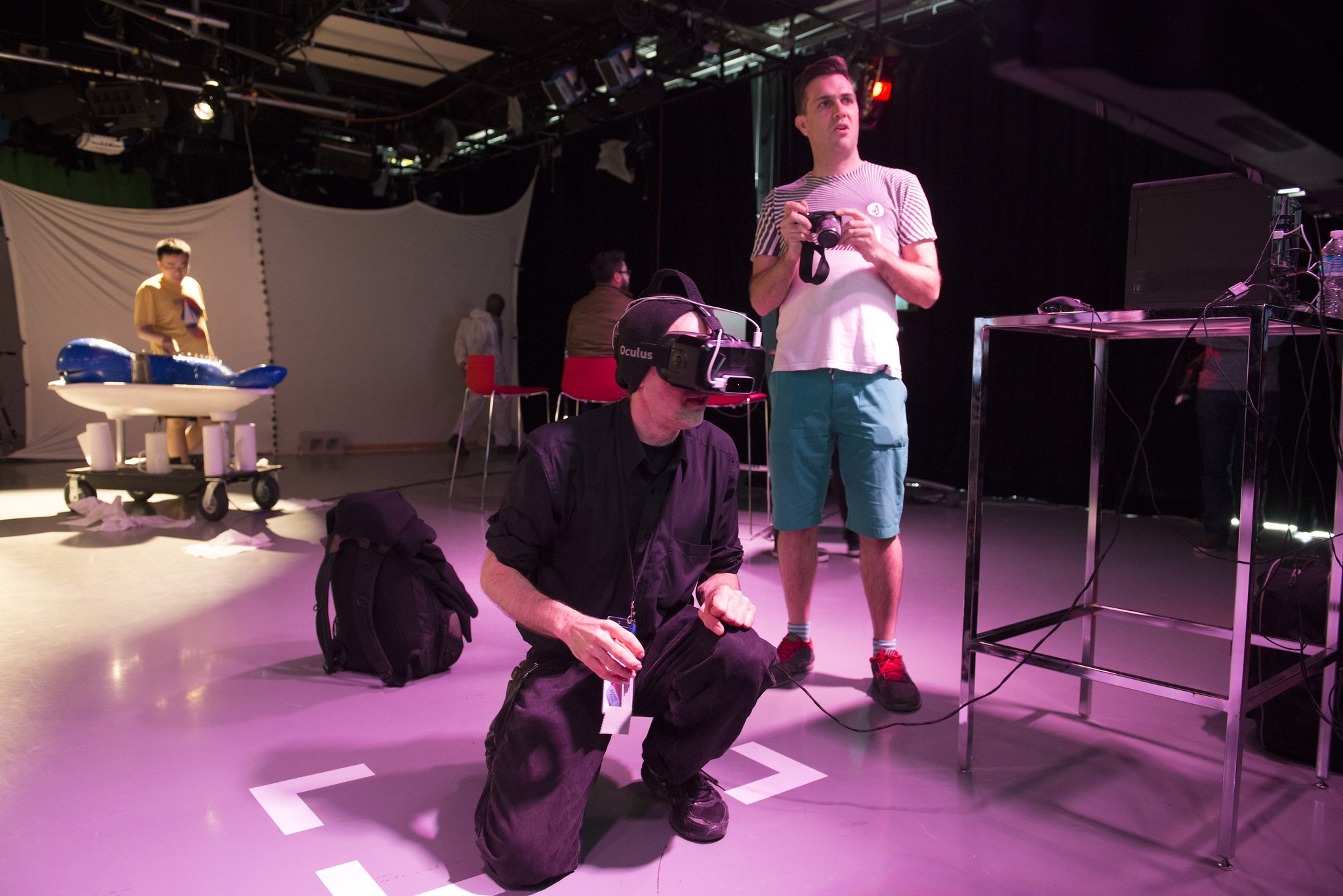A man is crouched down using a smart glasses device for viewing Augmented reality while another man is standing beside him watching the screen.