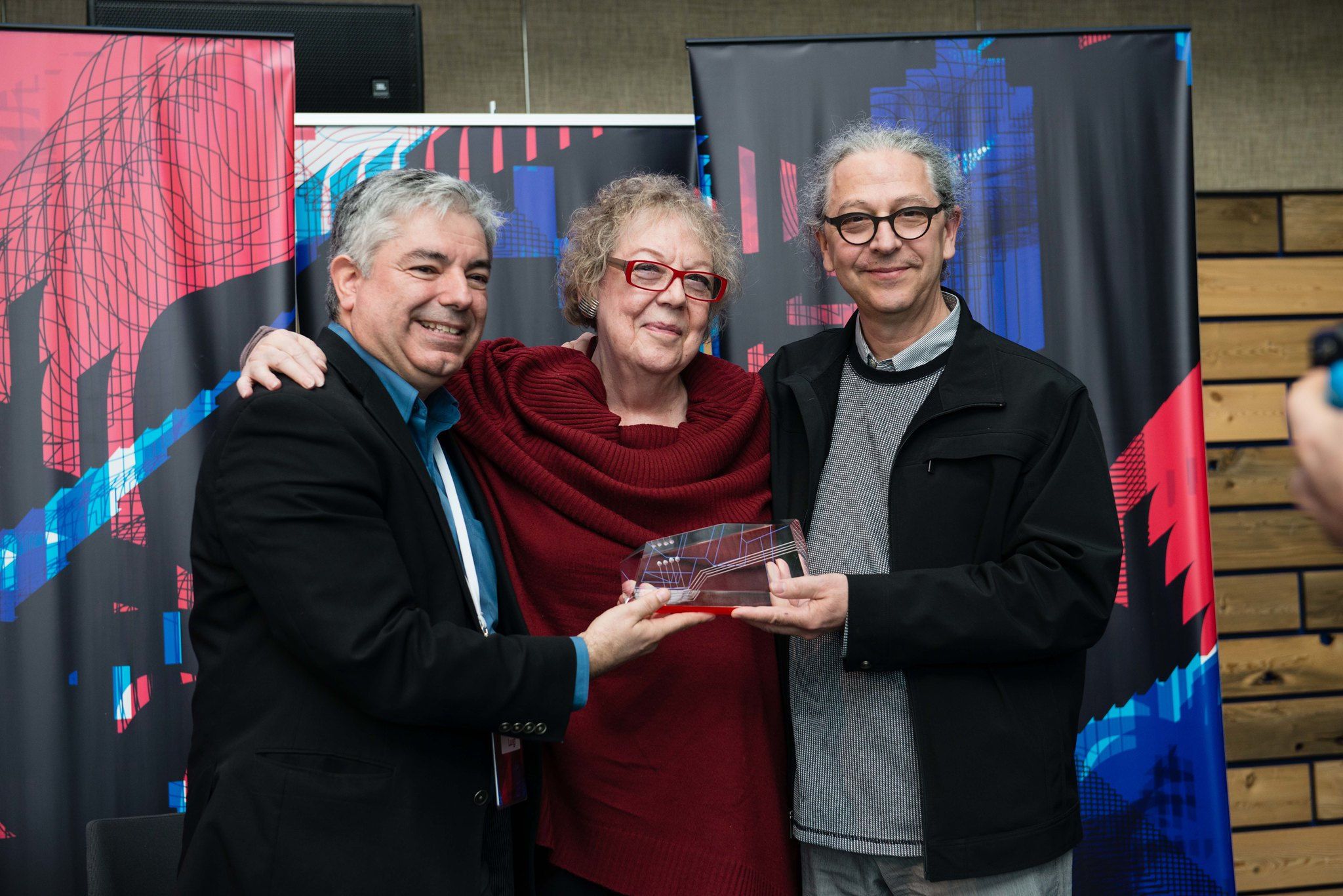 Presenting an award, three people standing together.