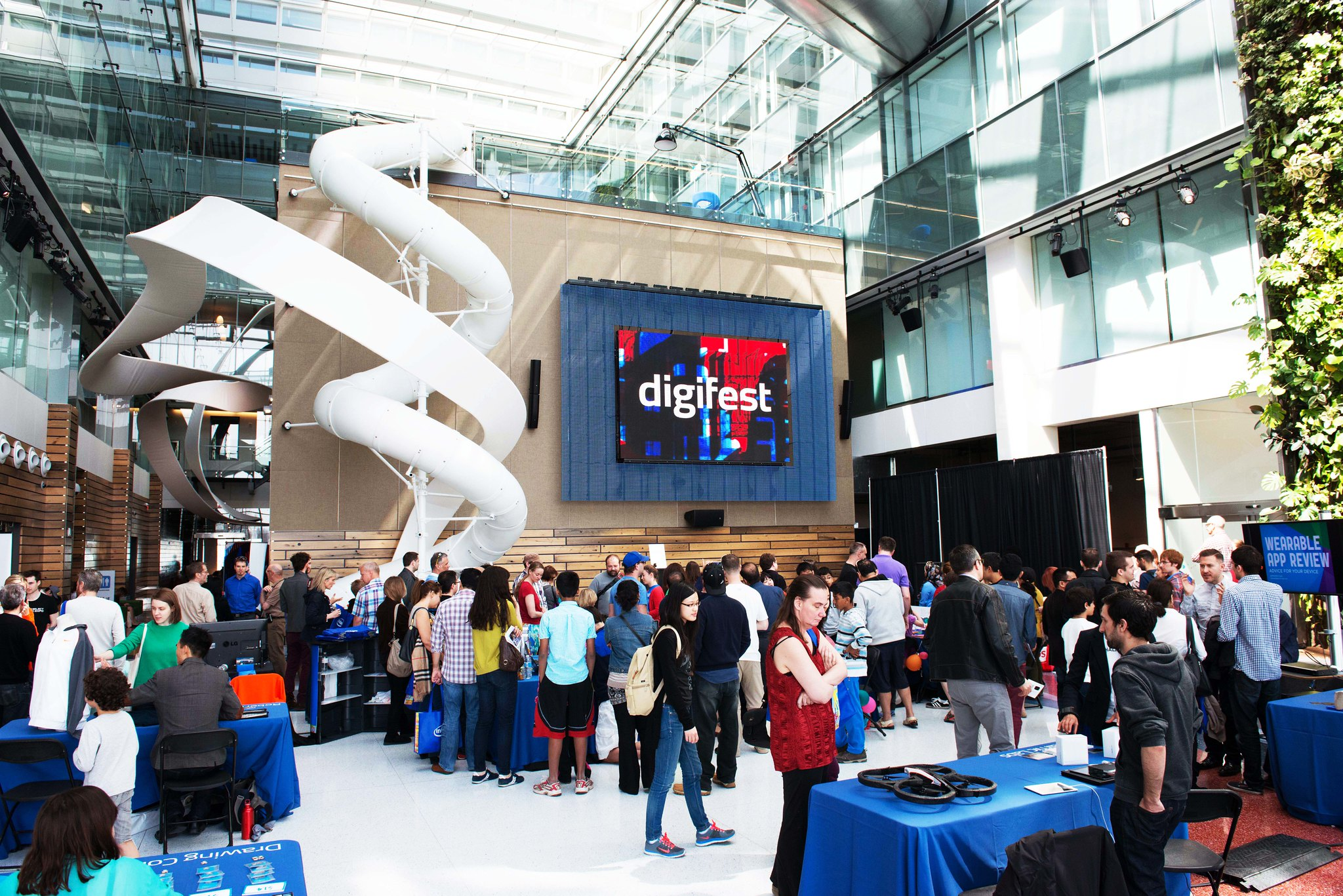 Digifest 2014, a large crowd of people standing around different table booths.
