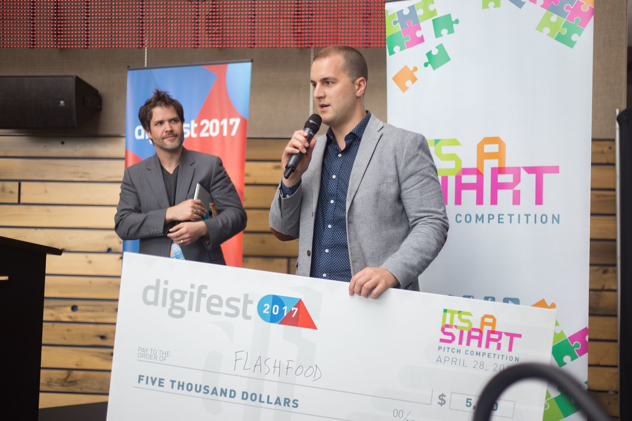 A winner of the it's a start competition giving a speech after receiving a $5000 cheque.