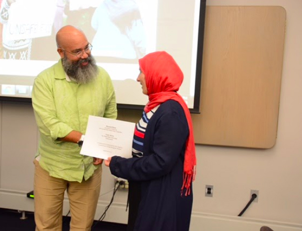 A woman accepting an award from a professor.
