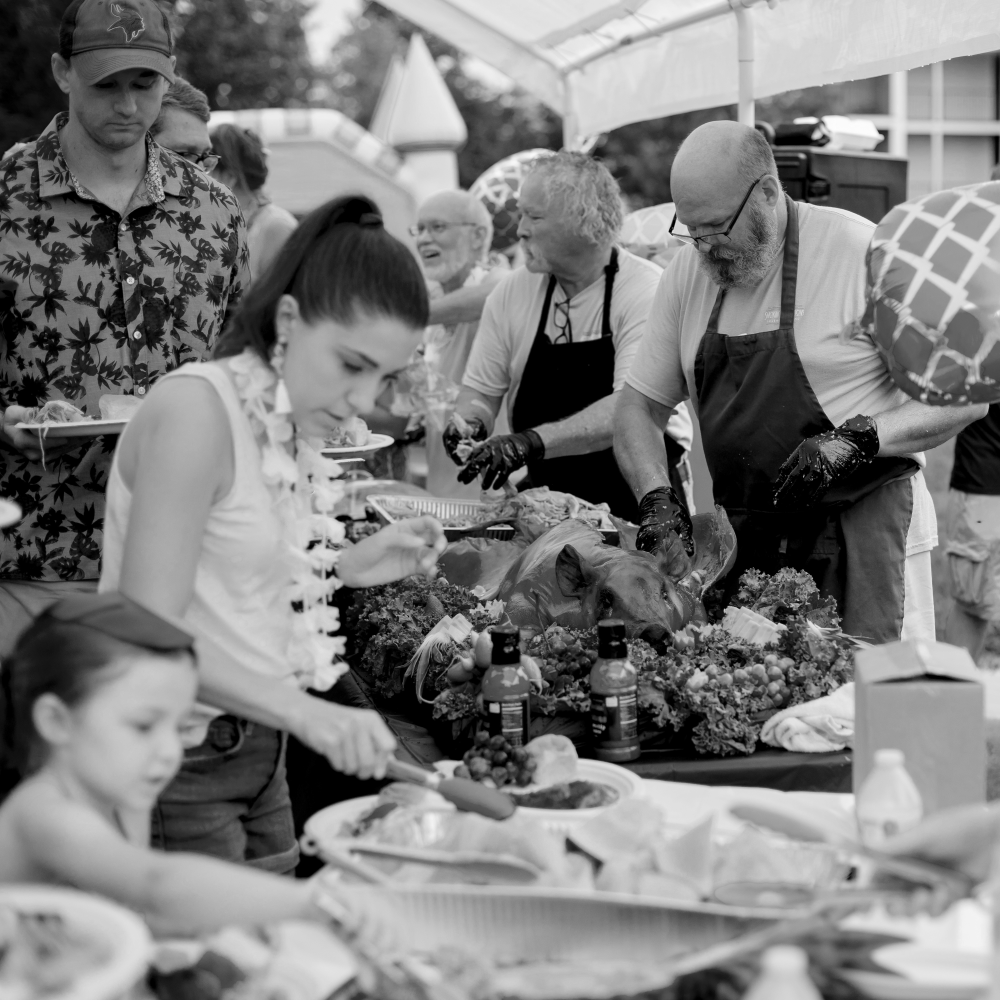 People serving a buffet dinner of roast pork and fresh fruit at a summer event