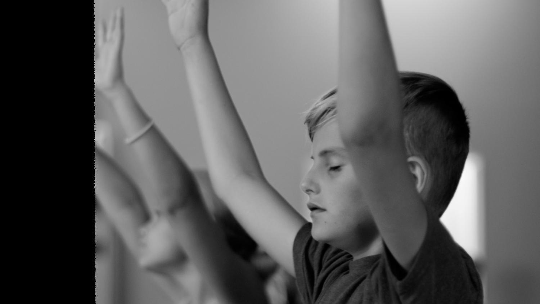 Kids raising their hands in worship