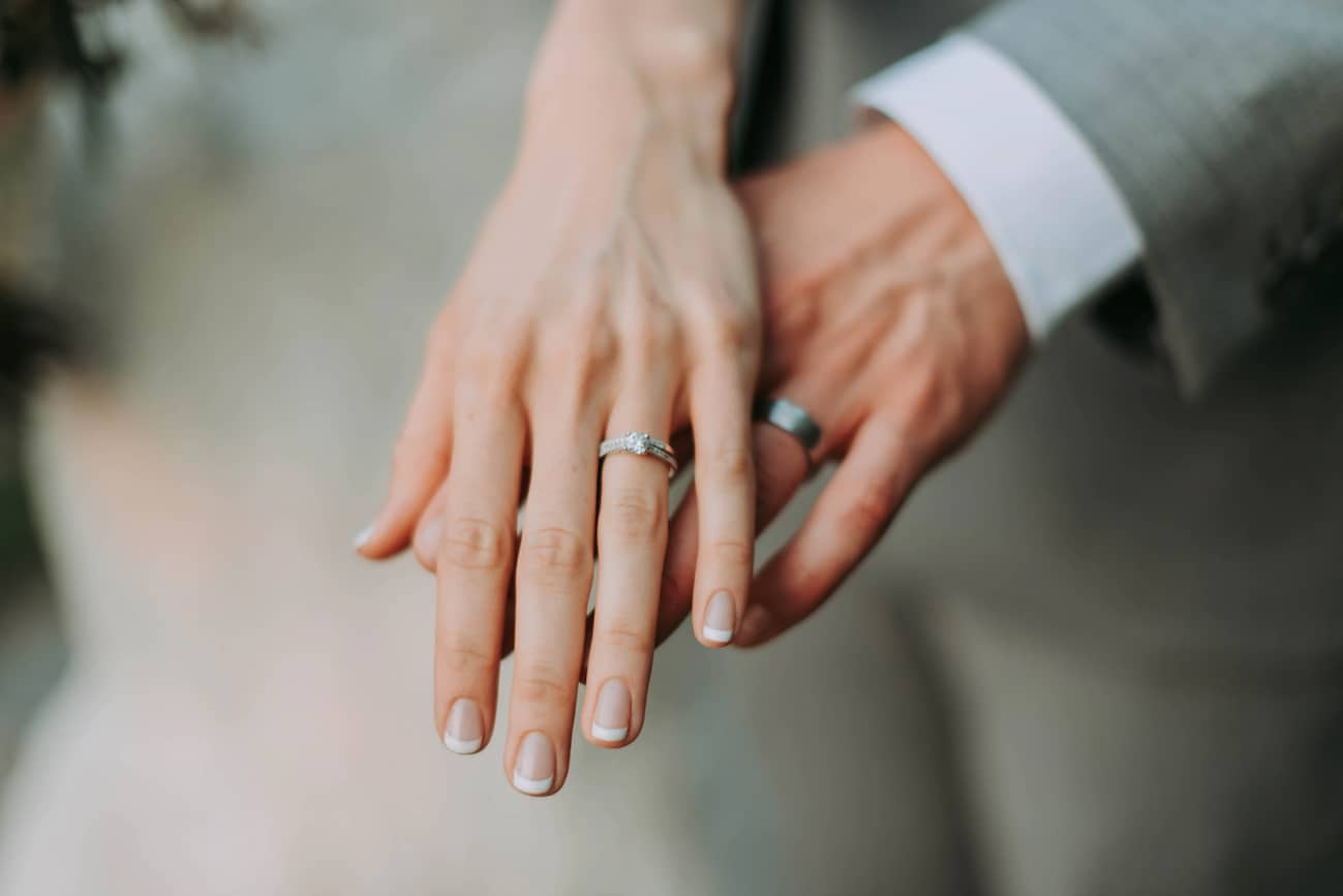 A man and a woman hold hands after exchanging wedding rings during their wedding ceremony