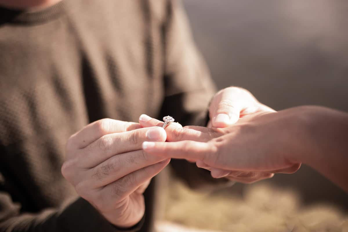 A man proposes to a woman with an engagement ring