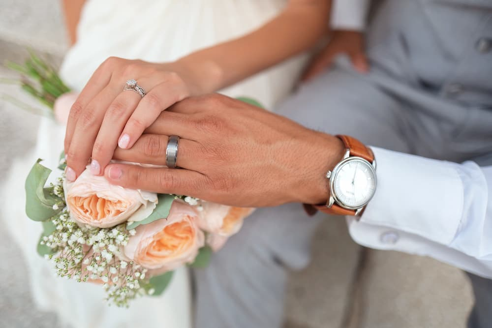 Woman wears a wedding ring followed by an engagement ring on her ring finger.