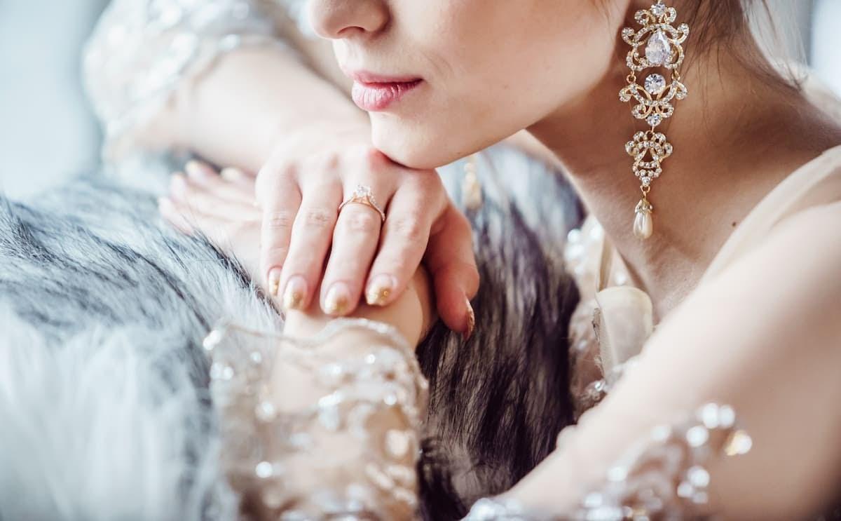 Bride wears beautiful gold earrings with diamonds on her wedding day