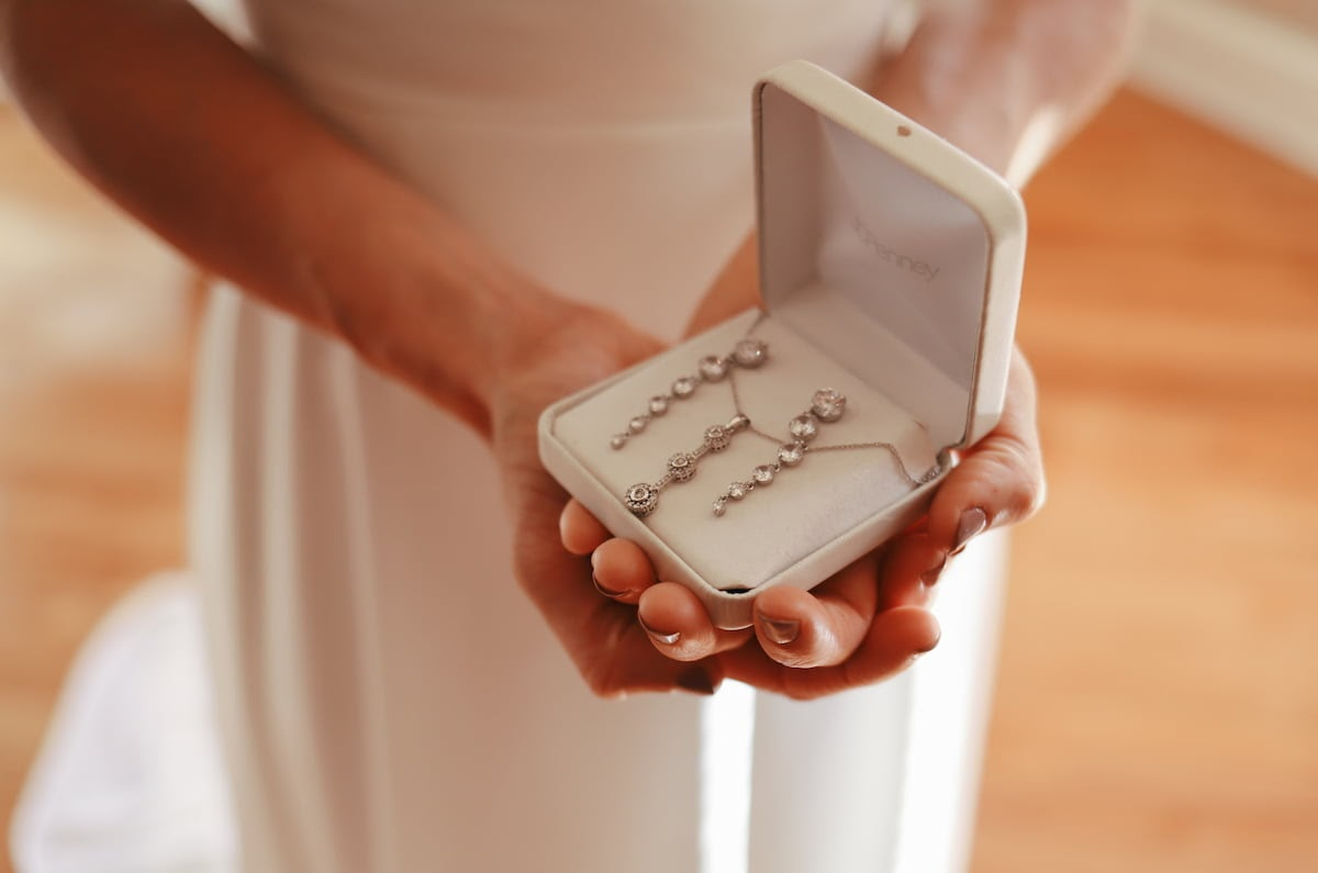 Bride gets ready to put on bridal jewelry on her wedding day