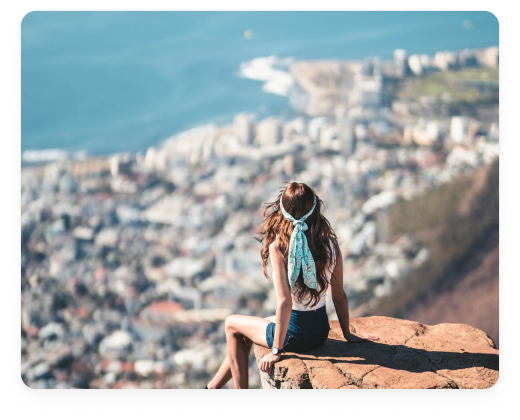Woman sitting on a ledge overlong a landscape