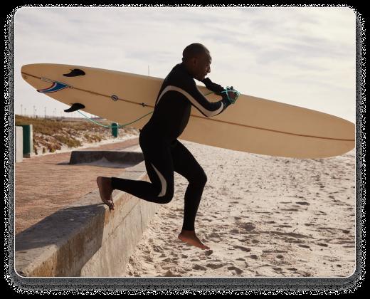 Man running towards a beech with surfboard