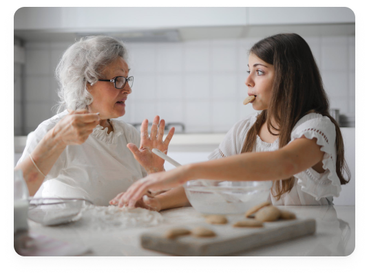 Old woman making cookies with a young woman eating cookies