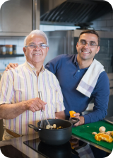 two men standing in a kitchen smiling while cooking