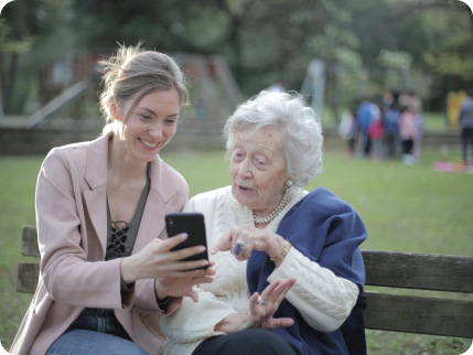 two woman sitting on a bench looking at mobile phone