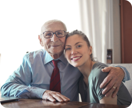 Old man hugging a young girl with brown hair and red lipstick