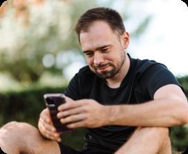 Man looking at his phone wearing a black t-shirt and shorts