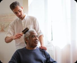 Man brushing an elderly mans hair