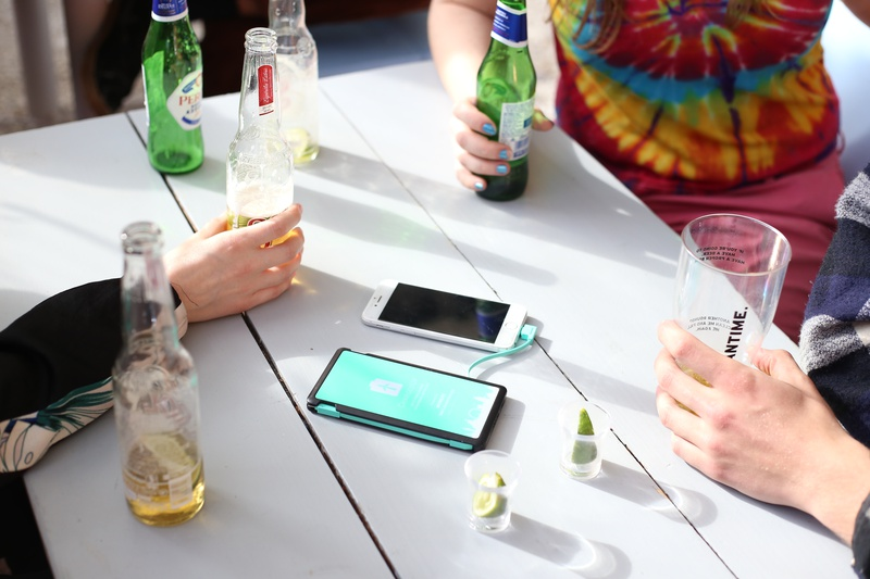 Group of people sitting around table, drinking and chatting while charging their phone