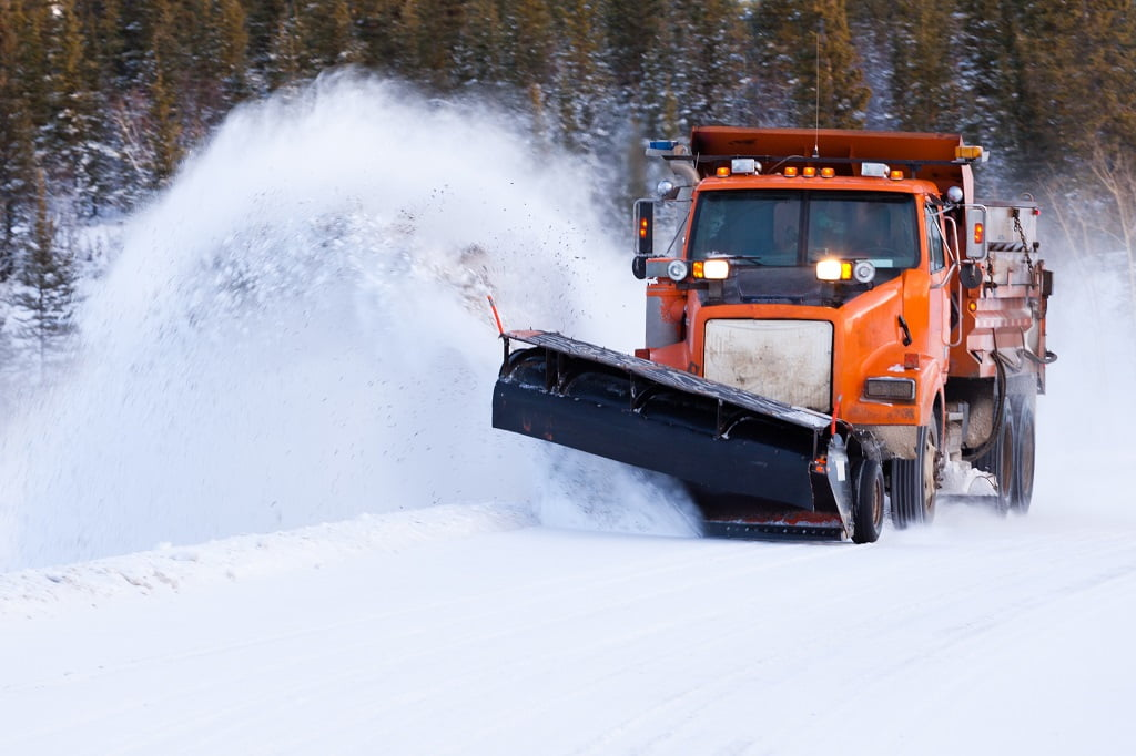 Snow plow truck clearing road after winter snowstorm blizzard for vehicle access