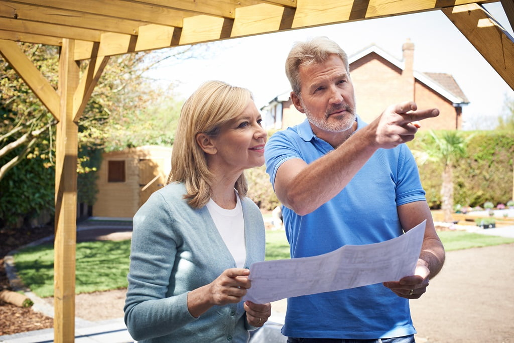 Mature Woman Discussing Plan With Landscape Gardener