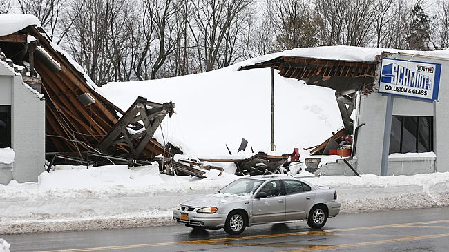 Snow build up on a business' roof causing it to collapse.