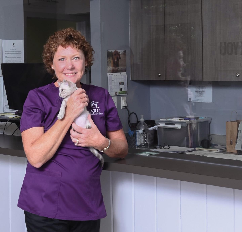 ARC employee holding a kitten in the office