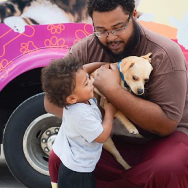 Man and child cuddling a small dog