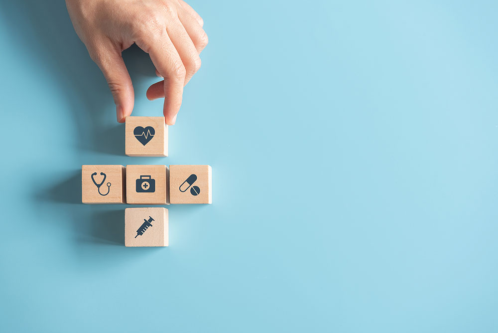 Photo of wooden blocks in shape of plus symbol. Each block contains an icon that relates to the healthcare field (for example: a stethoscope, medication, etc.).