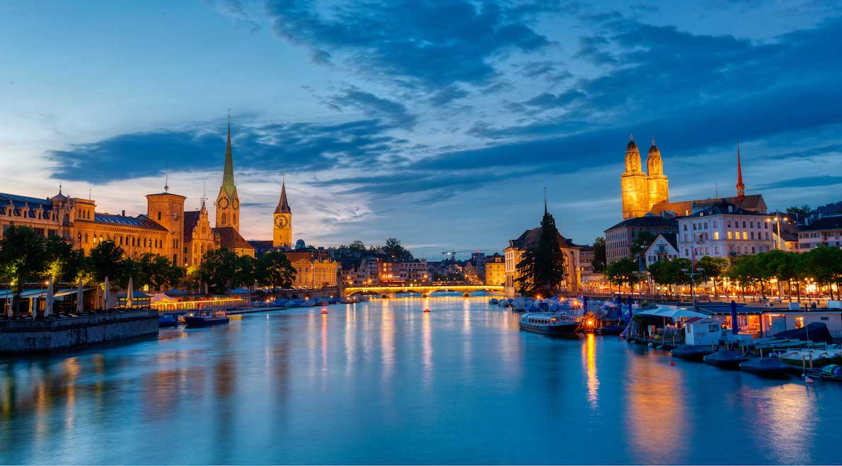 An image of the Zurich skyline and the Zurich lake by night.