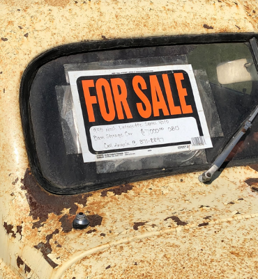 Fore sale sign on junk car